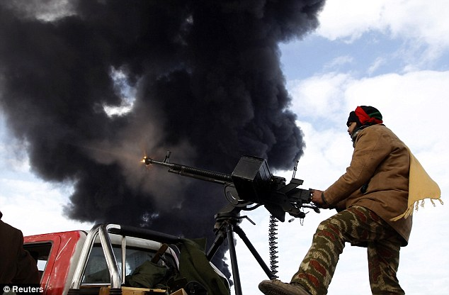 Heavy weaponry: A rebel fighter fires an anti-aircraft weapon in front of the burning has terminal