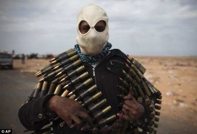 Fighting for their lives: A Libyan volunteer carries ammunition on the outskirts of the eastern town of Ras Lanouf