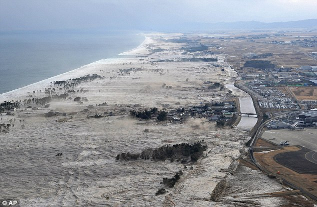 Terrifying: The tsunami slams into the shore line along Iwanuma in northern Japan after the 8.9 earthquake struck today