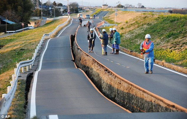 Split down the middle: Workers inspect a section of road that was torn in half by the force of the earthquake