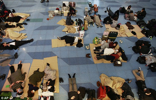Stranded: Hundreds of people were forced to make themselves at home on the floor of the Haneda Airport following the earthquake and tsunami