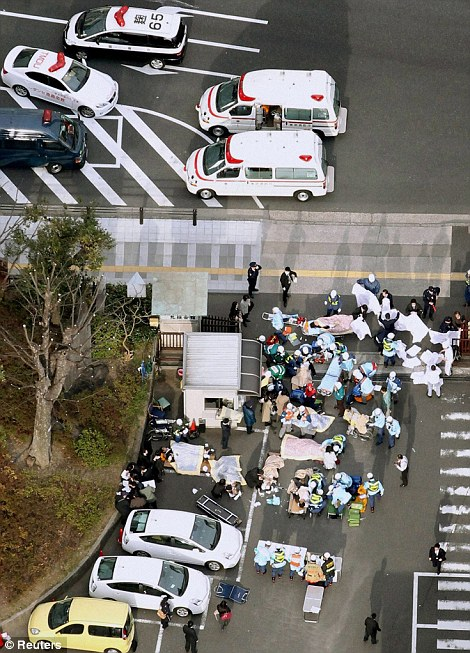 Injured people are attended to by emergency personnel after an earthquake in downtown Tokyo Japan March 11, 2011.