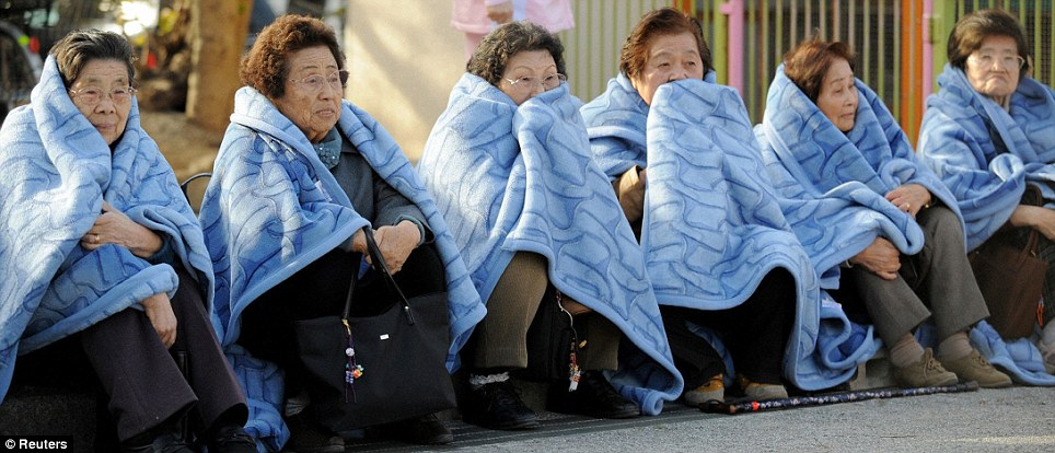 Cold: Elderly women who are likely to have expereinced a numbe rof earthquakes in their lifetime sit on the street as they take the most recent disaster which is one of the worst in recent history