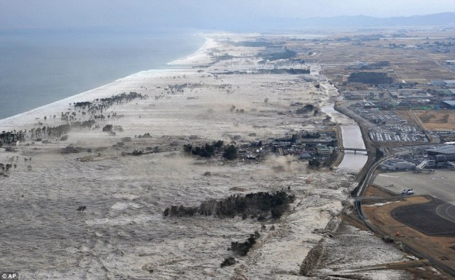 Washed away: Where there was once a coastline populated with homes and factories, powerful waves triggered by the tsunami devour anything in their path. Only a scattering trees remain