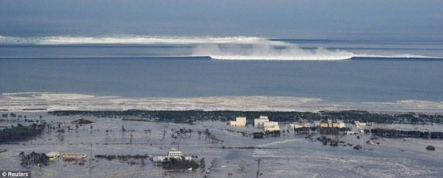 Horror: A huge wave is shown roaring in towards the coastal city of Natori in northwestern Japan