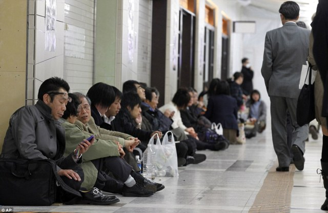 Stranded commuters sit inside Tokyo railway station as train services are suspended due to a powerful