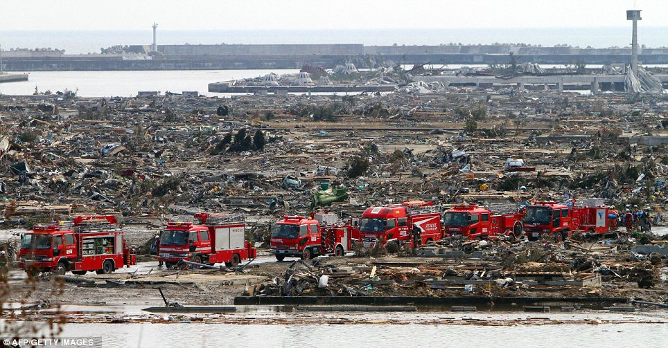 A convoy of emergency vehicles drive past rubble in Natory City
