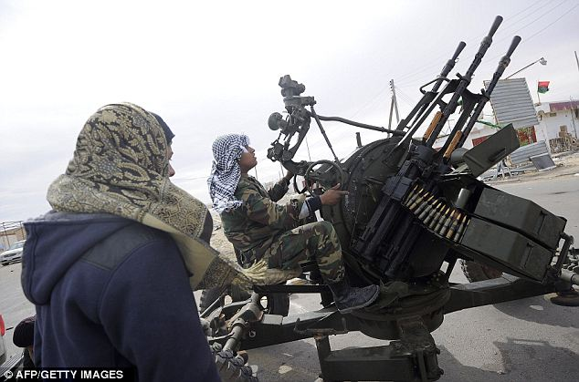 Libyan rebels man an anti-aircraft machine gun in Brega earlier today