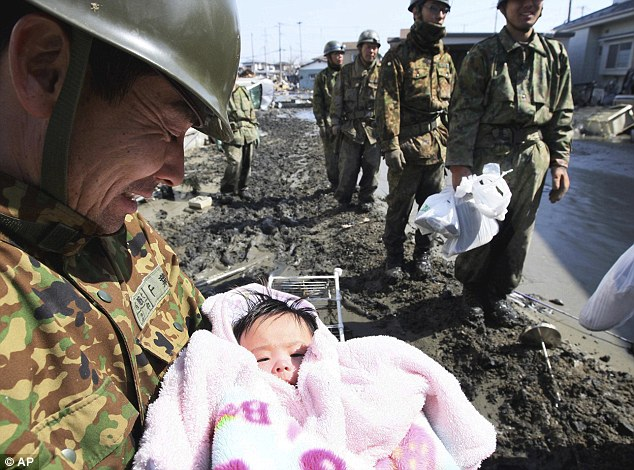 Joy: The member of Japan's Self-Defense Force member holds the four-month-old baby girl in Ishinomaki, northern Japan after her rescue