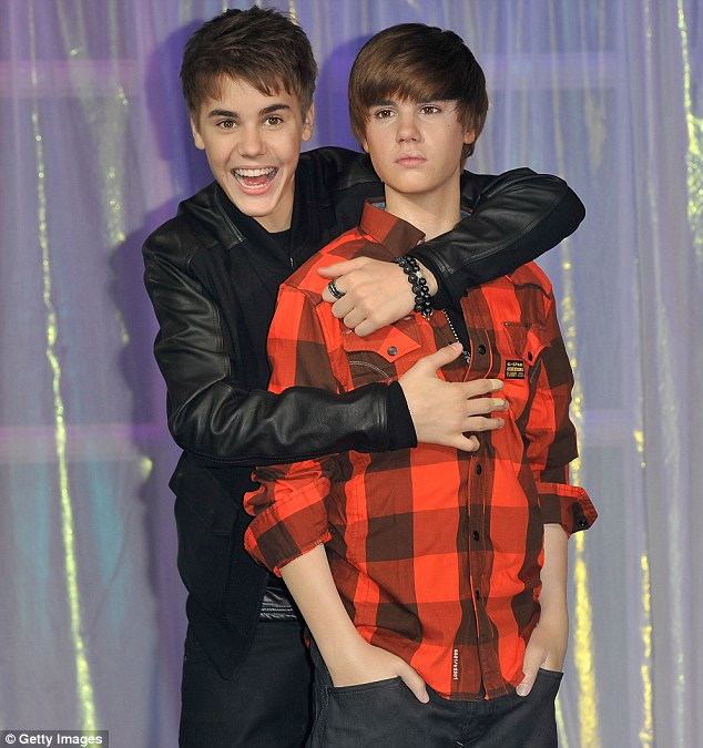 Who's that meant to be? Justin Bieber looks delighted with his waxwork at Madame Tussauds in London, despite the fact the model only bears a slight resemblance to the teen idol