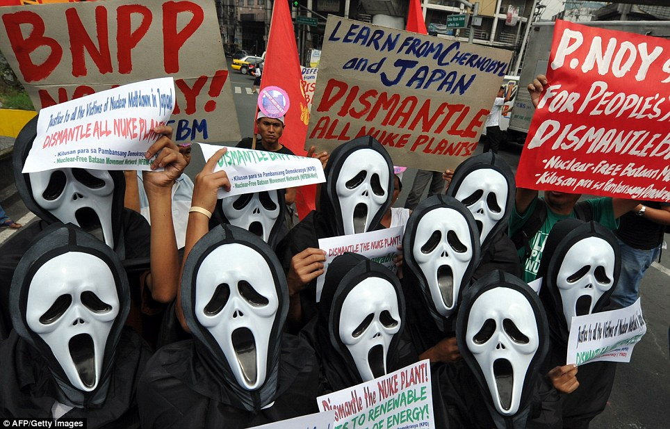 'Necer safe': Anti-nuclear activists wearing masks hold a protest today near the presidential palace in Manila in the Phillippines