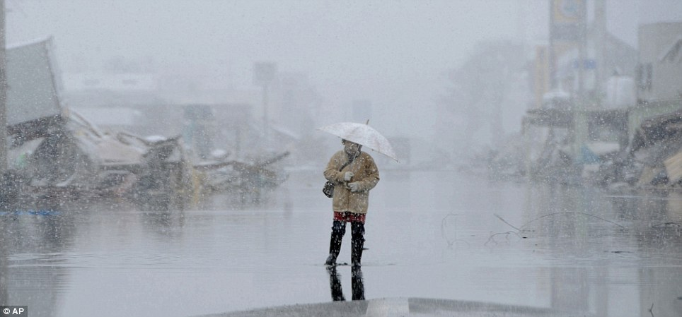Desolate: An elderly woman stands on a flooded street near her destroyed house at Ishinomaki, northeastern Japan, where 10,000 people are missing