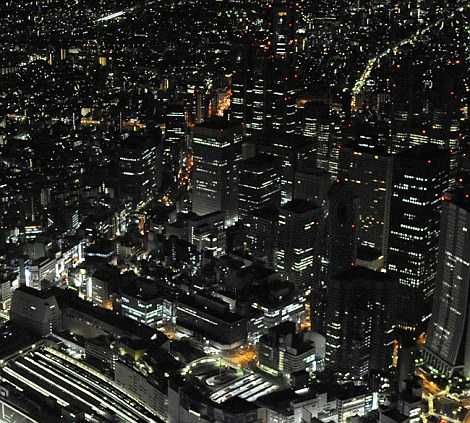Dimmer: Buildings in Tokyo turn down the lights as part of electricity saving efforts to avoid massive power outages