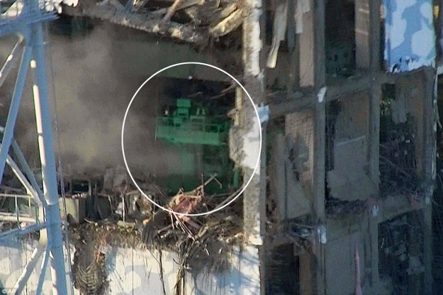 Exposed: A gaping hole is seen in the building of reactor number four at Fukushima plant in Japan. The green crane, circled, is normally used to move spent fuel rods into a 45ft storage pond, just out of shot. But the pool has now boiled dry