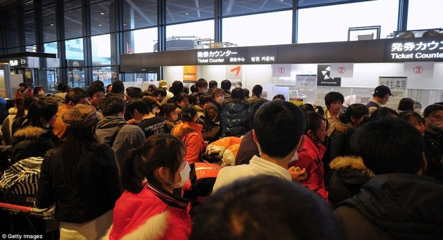 Fleeing: Passengers queue at the ticket counter to buy tickets for the earliest possible flight as they attempt to evacuate from Japan at Narita International Airport near Tokyo