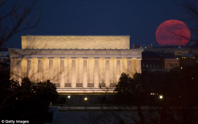 The full moon is seen as it rises near the Lincoln Memorial, in Washington DC