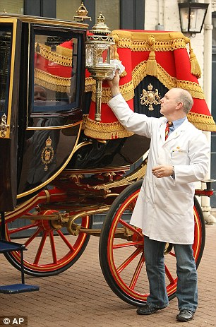 Carriage restorer, Dave Evans, cleans the side lanterns on the Glass Coach at the Royal Mews in central London