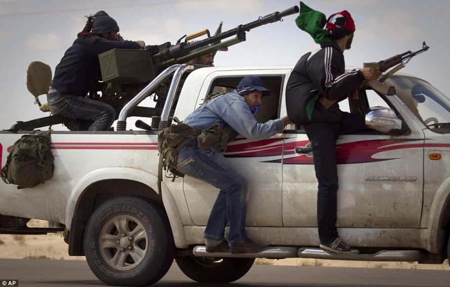 Unsure: Libyan rebels retreat from the outskirts of the city of Ajdabiya, south of Benghazi. Nato members are also fighting over who will take command of allied forces