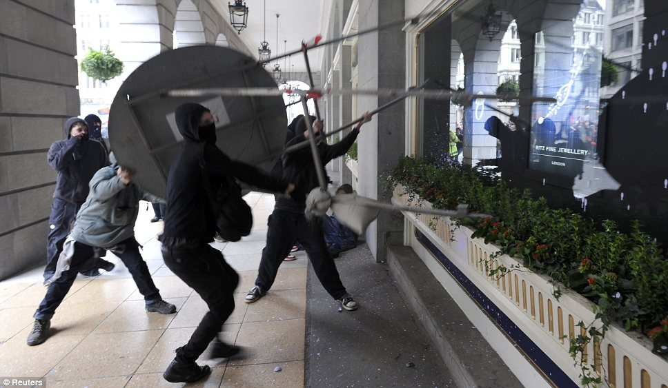 Civil disobedience: Demonstrators use a giant road sign to smash through a plate glass window at the Ritz Hotel