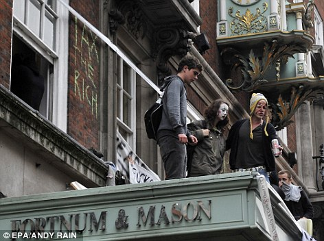 'Tax the rich': Protesters take to the roof of Fortnum & Mason and daub the building with graffiti