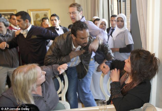 Financial Times journalist Charles Clover, centre, attempts to stop a Libya Ministry of Information official from grabbing Iman Al-Obeidi. She alleges she spent two days in detention after being arrested at a checkpoint in Tripoli