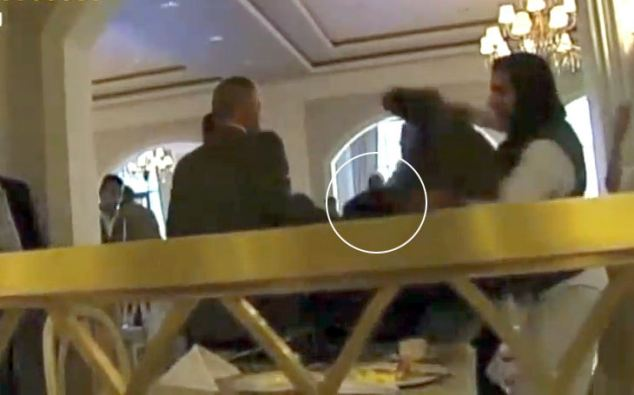 One of the hotel staff put a coat over Al-Obeidi's head as someone else holds her down