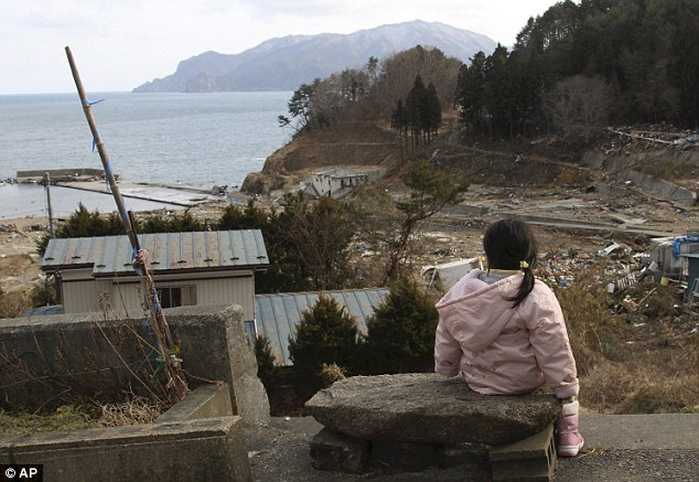 Heartbreaking: Manami Kon, 4, waits for her parents and younger sister who are still missing after the tsunami in Miyako
