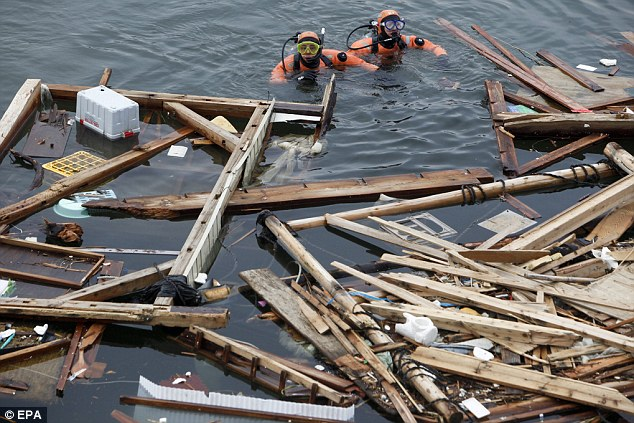 Search: Divers from the Japan Coast Guard look for bodies among the debris in Rikuzentakata
