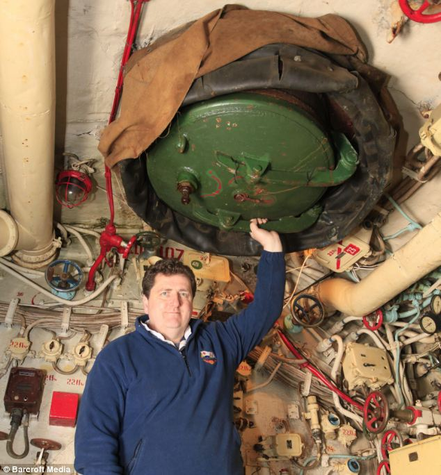 That sinking feeling: Mr Sutton demonstrates the escape hatch of the Black Widow submarine, which was built in Russia on April 1 1967