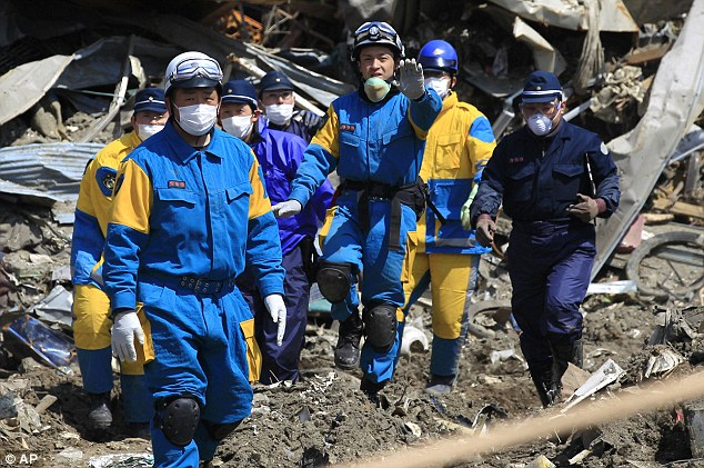 Recovery: Police officers carry the body of a victim from the rubble in Rikuzentakata, Iwate Prefecture, as the long search for the dead continues
