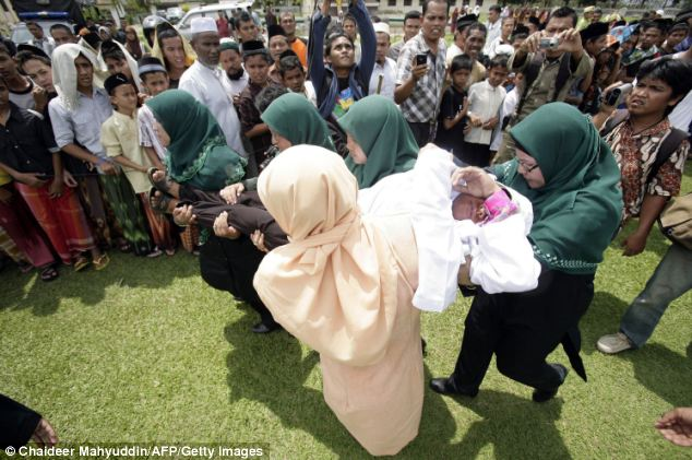 The jeering crowd take pictures and record Mukhtar being taken off the platform after she was whipped by Sharia police
