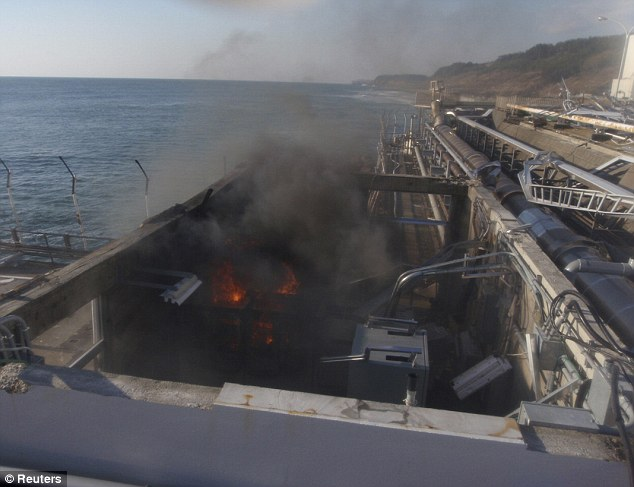 Threat: Fire and smoke are seen at a building for sampling from seawater near No. 4 reactor in this image taken today