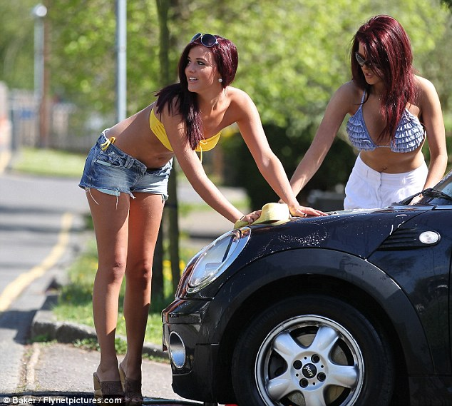 Working at the car wash: Lucy Mecklenbugrh gets to work on her car in the sun