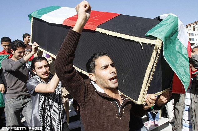Popular: Palestinians carry a symbolic coffin decorated with the Italian flag during a ceremony to mourn and denounce the kidnapping and killing Mr Arrigoni