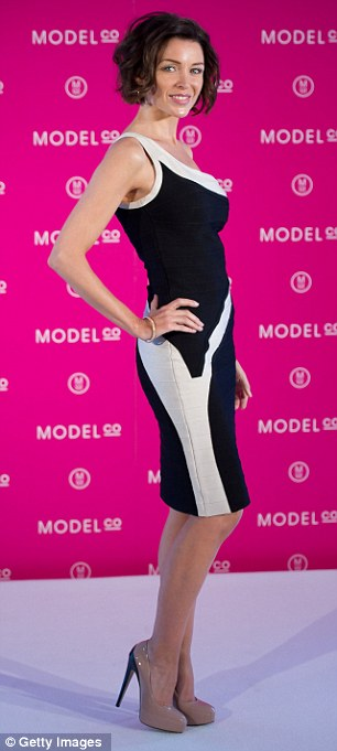 Black and white beauty: Dannii Minogue showed off her tiny frame in an asymmetrical monochrome dress as she launched a new beauty product in London today