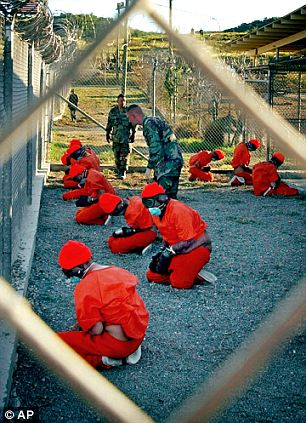 Held: Taliban and al-Qaeda detainees in orange jumpsuits sit in a holding area, watched by military police, at Camp X-Ray at Guantanamo Bay