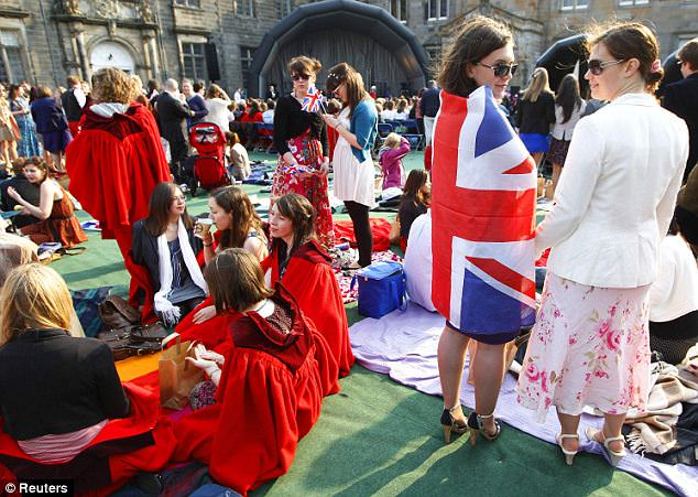 Wrapped in the flag: Revellers share a picnic breakfast in the quadrangle at St Andrews. A crowd of around 2,000, including locals, staff and students, were expected to attend the party