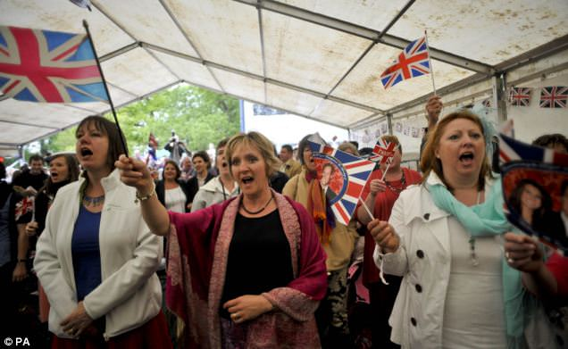 People wave flags and sing the National anthem as they watch the live TV broadcast on a screen in a marquee near Bucklebury