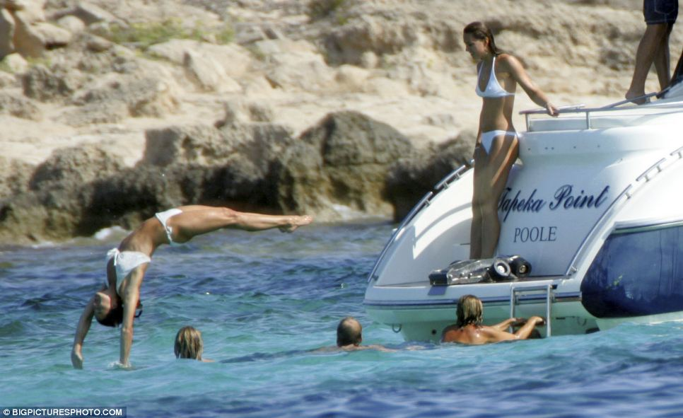 Athletic in Ibiza: Pippa Middleton performs a flawless backflip in to the warm waters of the Mediterranean as an admiring Kate looks on from the stern of the motor yacht