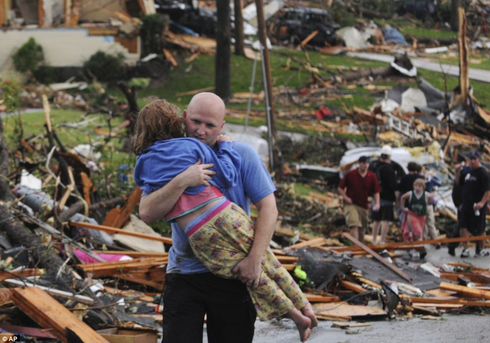 Re-united: A man carries a young girl who was rescued after being trapped with her mother in their home