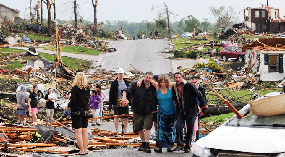 Community spirit: Residents of Joplin help a woman who survived in her basement after a tornado tore a path a mile wide and four miles long destroying homes and businesses