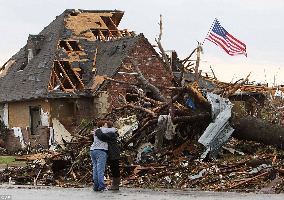Heartache: Two women fight back the tears as they hug in front of a house ripped apart by the tornado. In a symbolic show of strength, the U.S. flag flies from a tree behind them