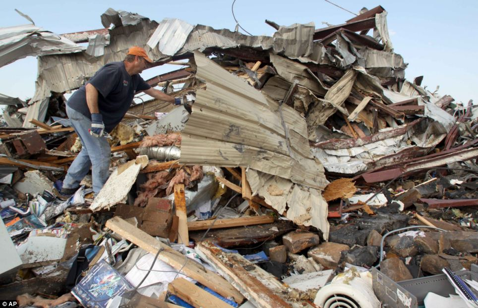 Searching: Matt Asbill digs through the wreckage of the office of his engineering business on the east side of Joplin