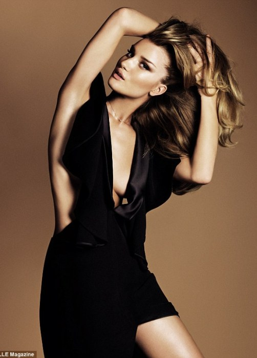 Supermodel: The British stunner posed in a revealing black silk dress which flashed her cleavage and thigh