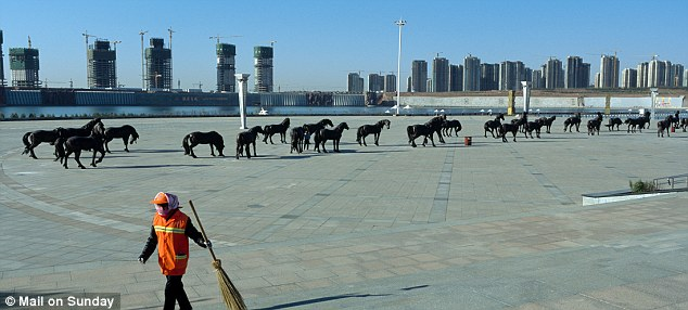 A cleaner works in in front of one hundred bronze horse bronze near the artificial river in Kangbashi district of the Chinese city of Ordos, Inner Mongolia