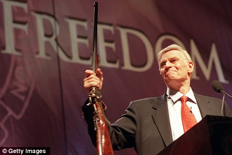 Former National Rifle Association (NRA) President Charlton Heston holding up a rifle during his address at the 131st NRA convention in 2002