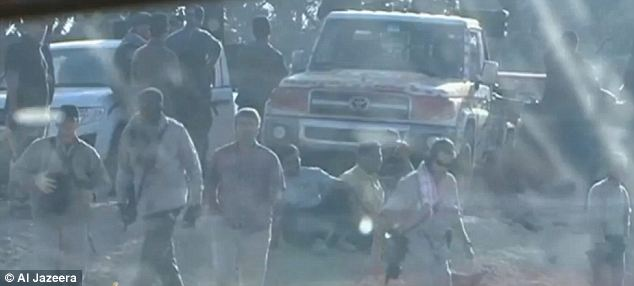 Special forces: The Western men are seen here walking away from the car and the pick-up truck, with the unarmed man in the pink T-shirt possibly an intelligence officer