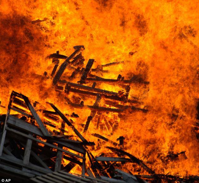 Raging: Residents burn wood to avoid it becoming flood debris
