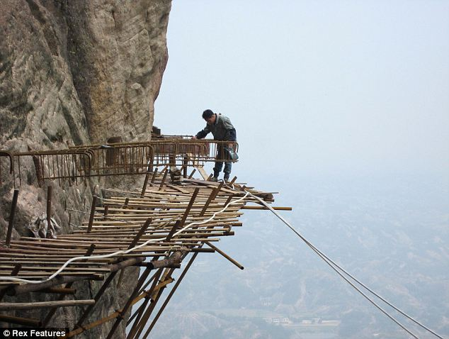 Don't look down: Teetering on the edge this builder inspects his handiwork