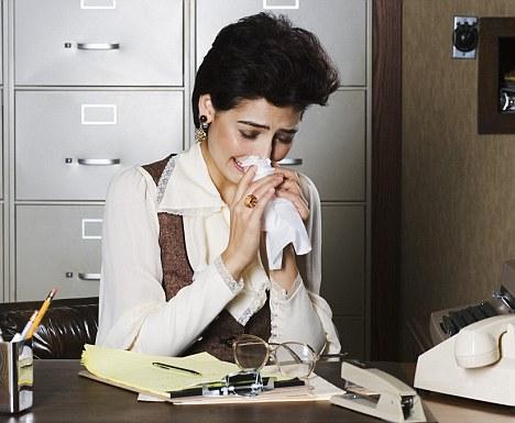 Un femme pleure à son bureau dans les années 1980.